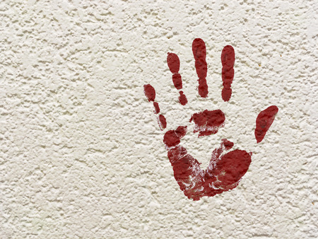 imprint of a red palm on a white concrete wall