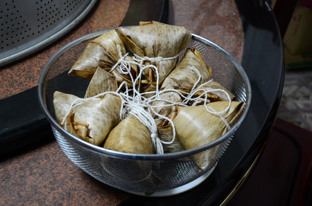 Traditional Dragon Boat Festival food concept unwrapping zongzi or rice dumpling. Asian food steamed sticky rice dumpling with fillings wrapped in reed leaves.