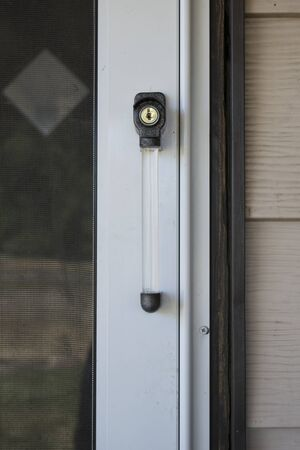 Close view of a metal and clear plastic storm door handle. Stock fotó