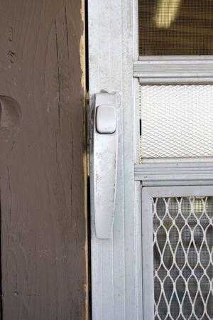Close view of a crude looking metal screen door handle.