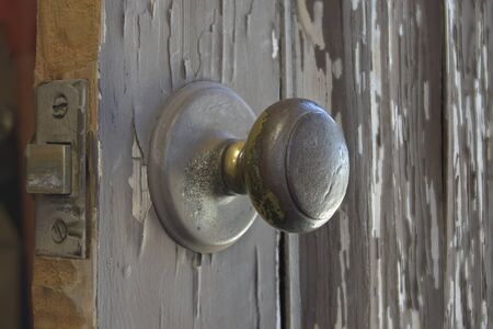 Close view of an old beat up well used brass door knob on a wooden door with peeling paint.