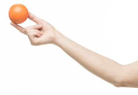female hand with orange sponge ball, isolated on white photo
