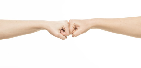 fist fight: Two female fists hitting each other, isolated on white Stock Photo