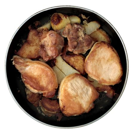 Roasted pork and shatters of potatoes on frying-pan photo