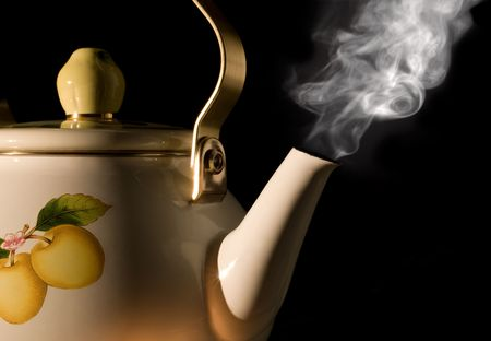 Tea kettle with boiling water on black background photo