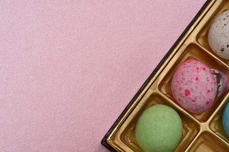 patterned chocolate ball in box on pink paper background