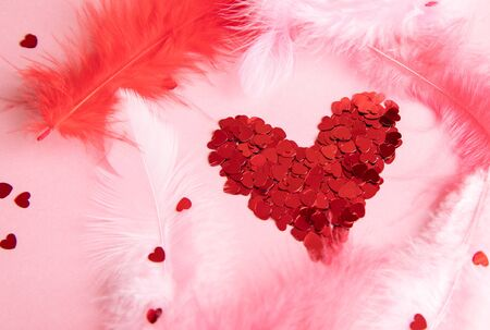 confetti heart on a pink background with feathers