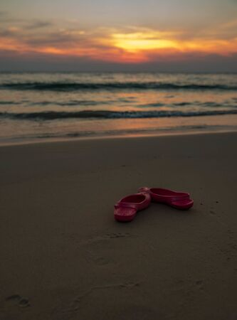 pink rubber shoes by the sea against the sunset in Thailand 免版税图像