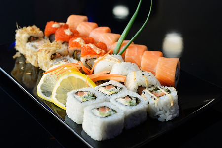 Japanese sushi on a black plate.
