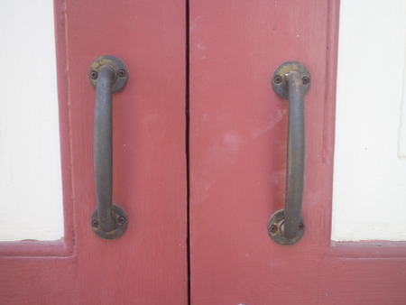 Closeup image of old wooden door with metal knob and rusty bolt  photo