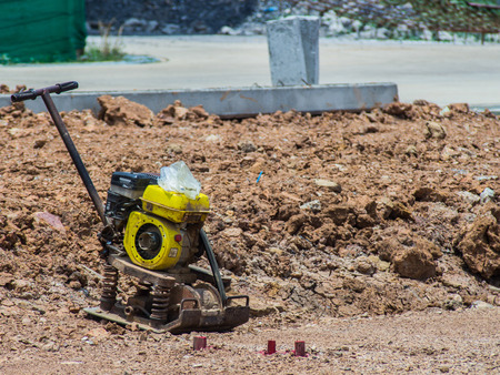 quoted: Vibrating Plate Machine put on the yellow soil compaction has not quoted. Stock Photo