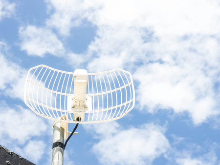 homestyle: A roof mounted home-style satellite dish with blue sky.