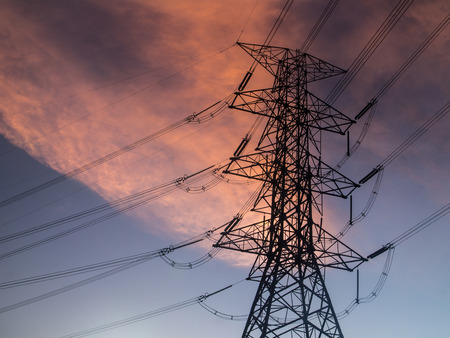 Silhouette of electrical pylon over blue sky photo
