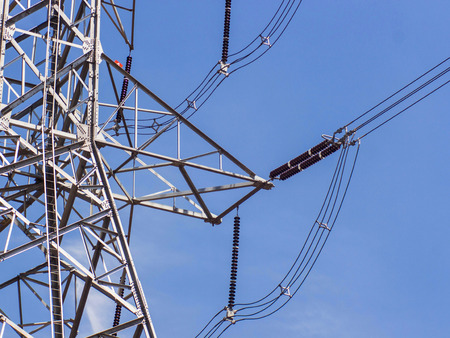 a high voltage power pylons against blue sky photo