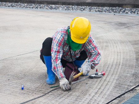 hobnail: hobnail in a Concrete and a yellow  hammer Stock Photo