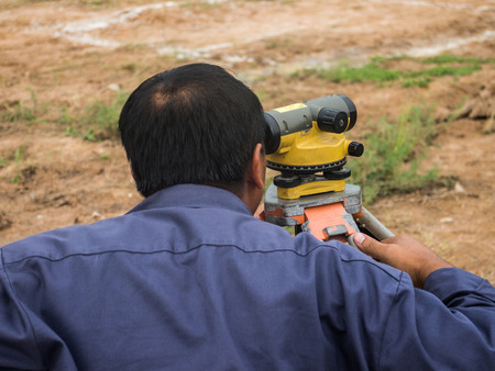 Surveying measuring equipment level theodolite on tripod at construction site