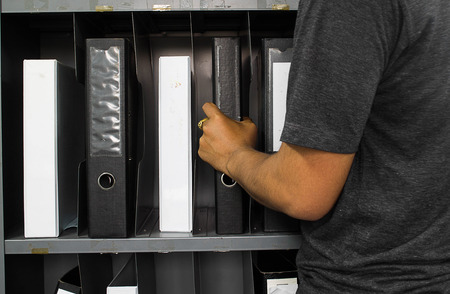 hand catch File folders, standing on the shelves at office 版權商用圖片