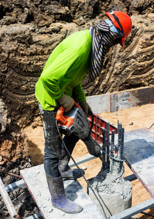 mounter: Portarait of positive Builder worker with pneumatic hammer drill equipment at construction site Stock Photo