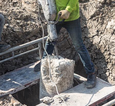 Man drilling cement concrete stake. photo