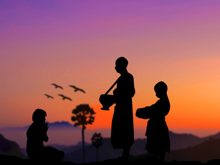 Silhouette people put food offerings in a Buddhist monks alms bowl for good merit