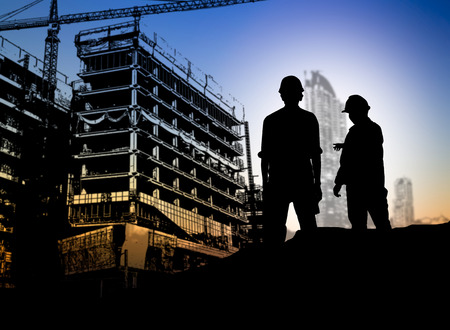 silhouette engineer looking blueprint in a building site over Blurred construction site 版權商用圖片 - 42158669