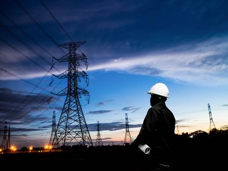 energia electrica: silueta de ingenieros de pie en la estación de energía eléctrica