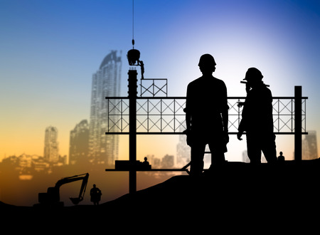 silhouette engineer looking blueprint in a building site over Blurred construction worker on construction site