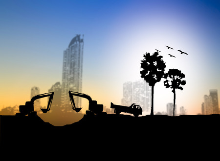 loaders: silhouette  Loaders and trucks in a construction site over Blurred construction site Stock Photo