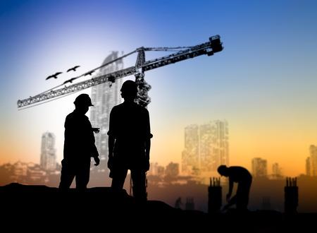 camion grua: construcción silueta ingeniero más trabajador de la construcción borrosa en el sitio de construcción Foto de archivo