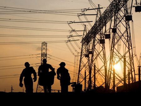 building silhouette: Silhouette of engineer looking at blueprints in a building site over Blurred substation