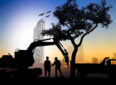 loaders: silhouette worker with Loaders and trucks in a building site over Blurred city Stock Photo