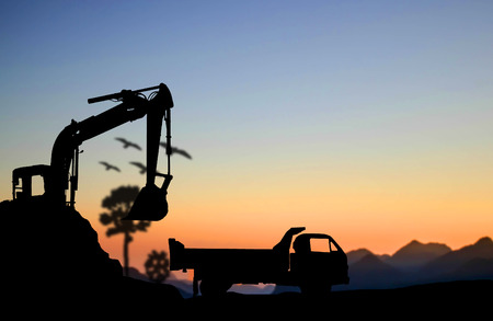 silhouette Excavator and truck working at construction site