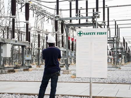 Engineers standing at electricity station and white sign Imagens