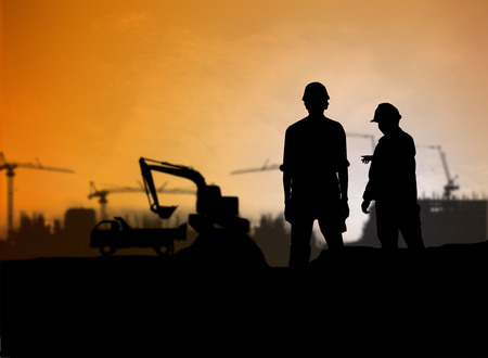 loaders: silhouette engineer looking Loaders and trucks in a building site over Blurred construction worker on construction site
