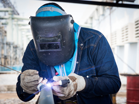 Welder on galvanized pipe in shop at substation Standard-Bild