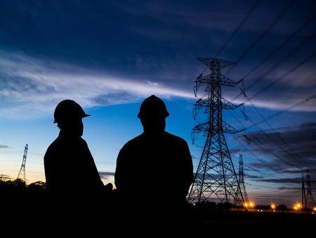 silhouette of two engineers standing at electricity station