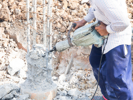 mounter: Builder worker with pneumatic hammer drill equipment breaking stake at construction site