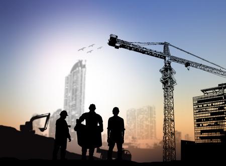 operarios trabajando: ingeniero de la silueta que mira modelos de obras de construcción borrosa
