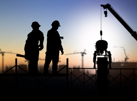 construction site helmet: silhouette engineer looking a building site over Blurred construction worker on construction site