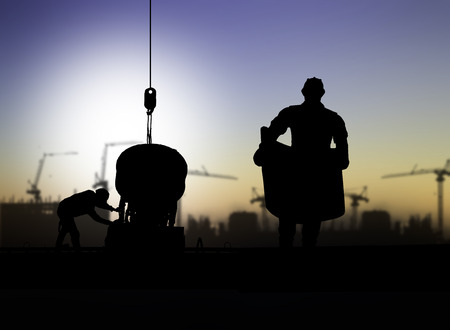 construction site helmet: silhouette engineer looking at blueprints in a building site over Blurred construction worker