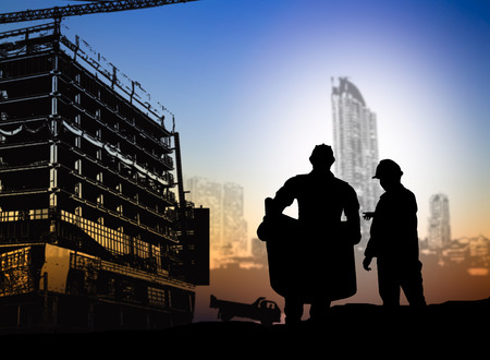 silhouette engineer looking blueprint in a building site over Blurred construction site