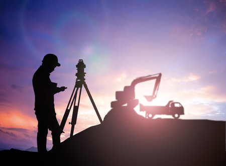 survey: silhouette survey engineer working  in a building site over Blurred construction worker on construction site Stock Photo
