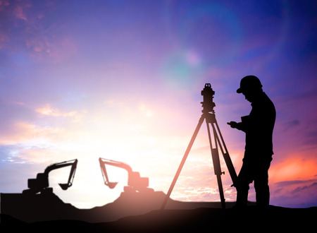 land surveying: silhouette survey engineer working  in a building site over Blurred construction worker on construction site Stock Photo