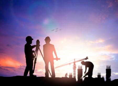 topografo: ingeniero encuesta silueta trabajando en una obra de construcción más trabajador de la construcción borrosa en el sitio de construcción