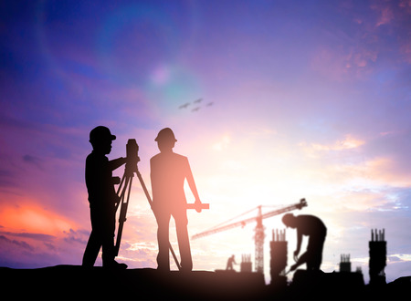 surveyor: silhouette survey engineer working  in a building site over Blurred construction worker on construction site Stock Photo