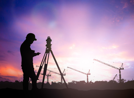 silhouette survey engineer working  in a building site over Blurred construction worker on construction site Standard-Bild