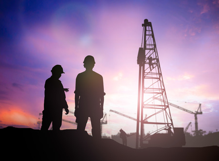 building silhouette: silhouette engineer looking work a building site over Blurred construction worker on construction site
