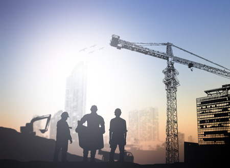 construction crane: silhouette engineer  in a building site over Blurred construction site Stock Photo