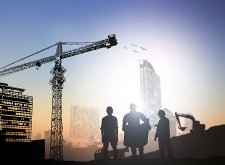 architect drawing: silhouette engineer  in a building site over Blurred construction site Stock Photo