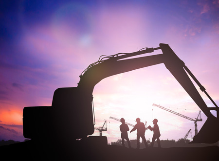 job site: silhouette engineer  in a building site over Blurred construction site Stock Photo